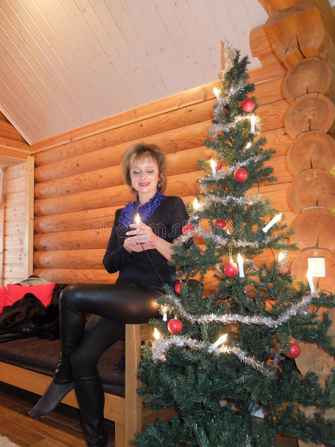 Woman at the Christmas tree. The woman at Christmas tree cottage for a weekend getaway. Finland royalty free stock images