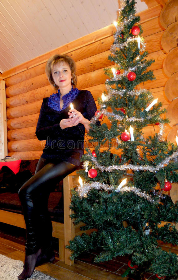 Woman at the Christmas tree. The woman at Christmas tree cottage for a weekend getaway. Finland stock photo
