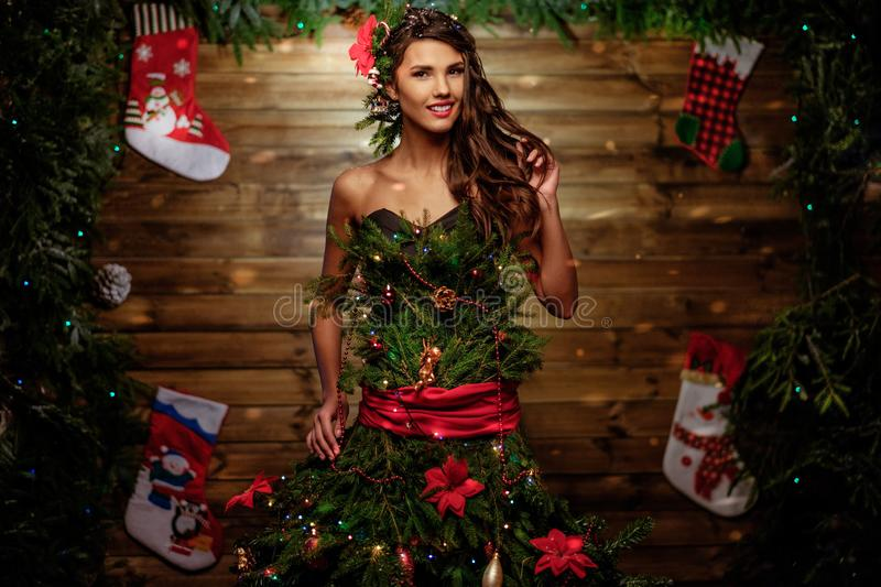 Woman in Christmas tree dress with glass of champagne and sparkler.  stock images