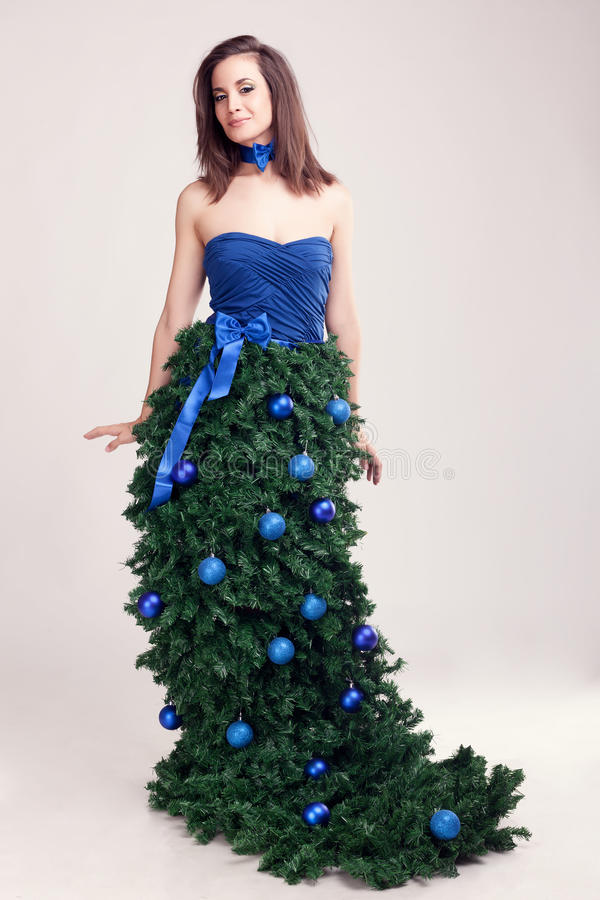 Woman in christmas tree dress on grey background. Beauty and fantasy concept royalty free stock image