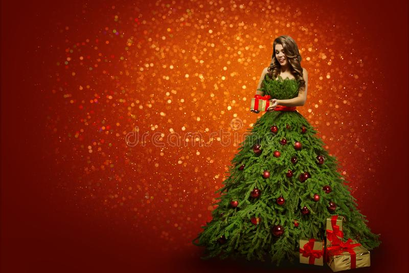 Woman in Christmas Tree Dress Holding Present Gift, Fashion Girl. Standing over Red lights New Year Background stock image