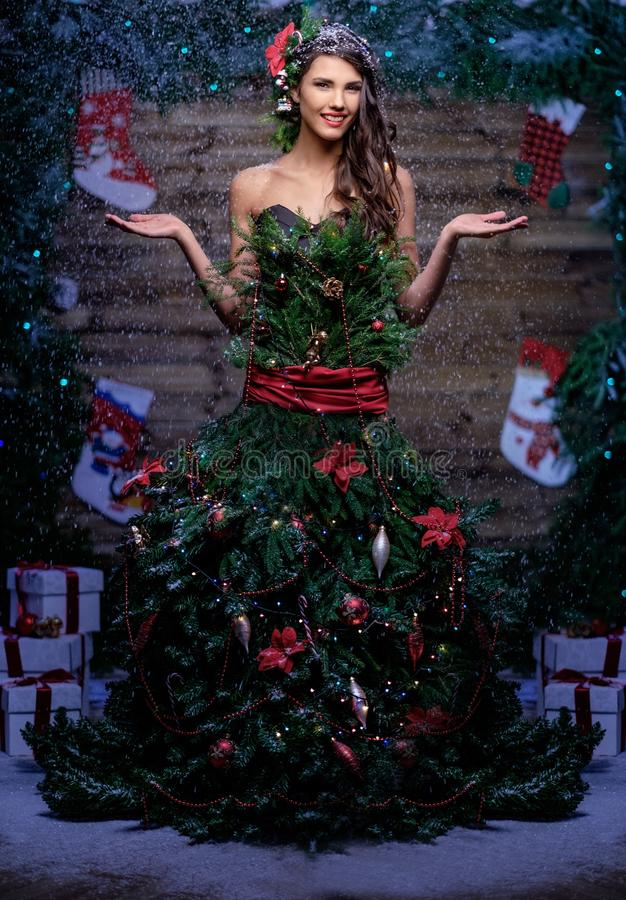 Woman in christmas tree dress. Standing under snow stock image
