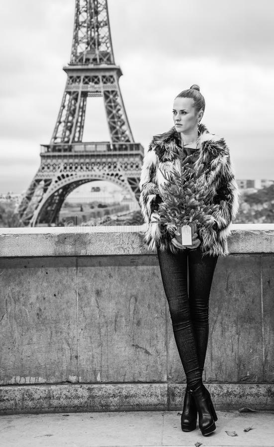 Woman with Christmas tree in front of Eiffel tower. The Party Season in Paris. Full length portrait of trendy woman with Christmas tree in fur coat in the front royalty free stock photo