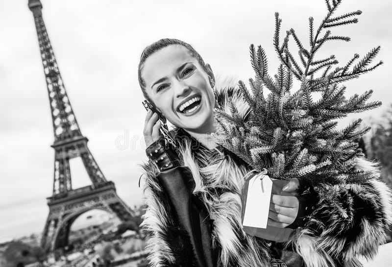 Woman with Christmas tree in Paris, France using cell phone. The Party Season in Paris. happy modern woman with Christmas tree in fur coat in Paris, France using stock photos