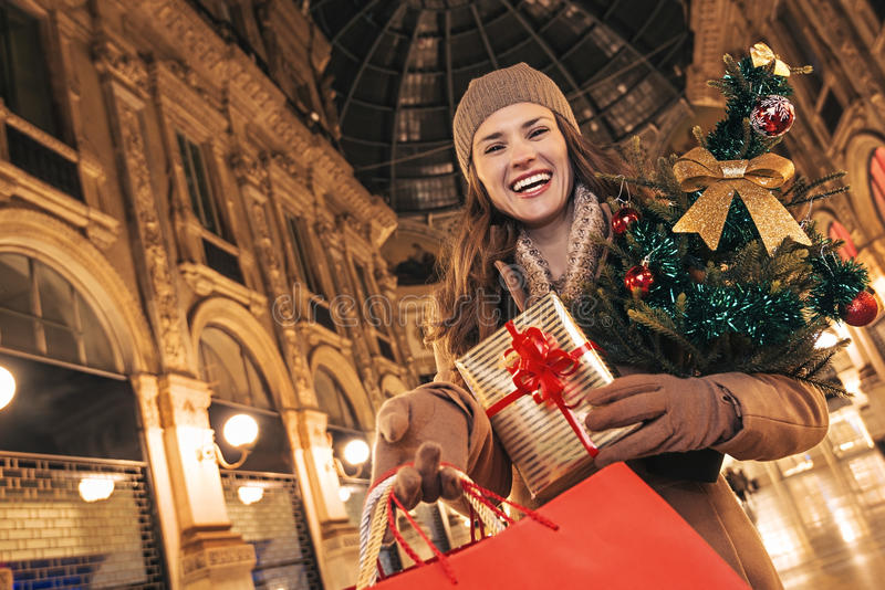 Woman with Christmas tree showing shopping bags in Milan. On a huge Christmas sales in Italian fashion capital. smiling modern traveller woman with Christmas stock photo