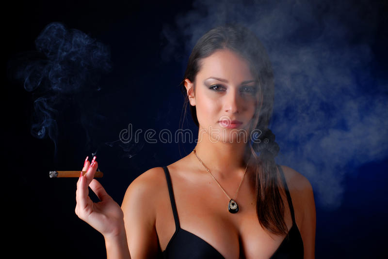 Woman with cigar. Portrait of beautiful brunet woman with cigar stock image