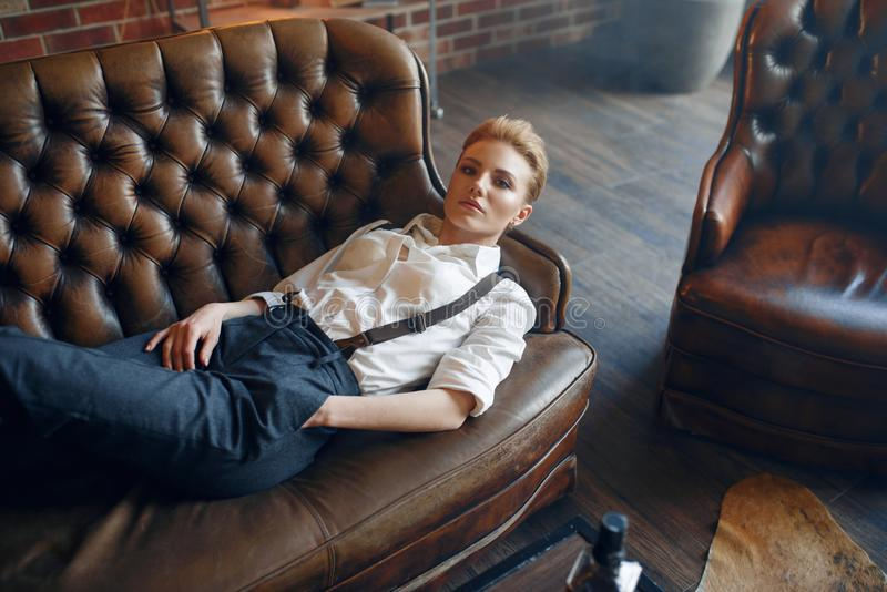 Woman with cigar lying on couch, retro fashion royalty free stock images