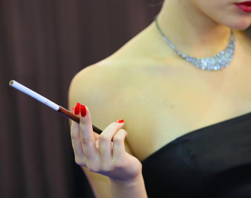 Woman with a cigarette. Manicure red stock photo