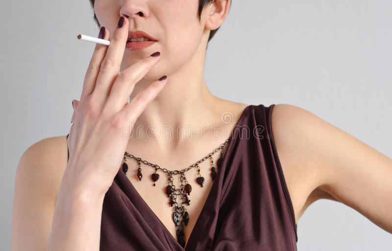 Woman and cigarette. Woman puts a thin cigarette to his lips stock photo