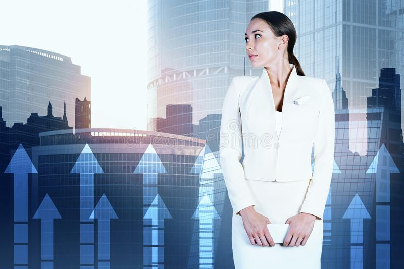 Woman in city with arrows. Attractive young european businesswoman standing on abstract city background with upward arrows. Success and economy concept. Double royalty free stock photos