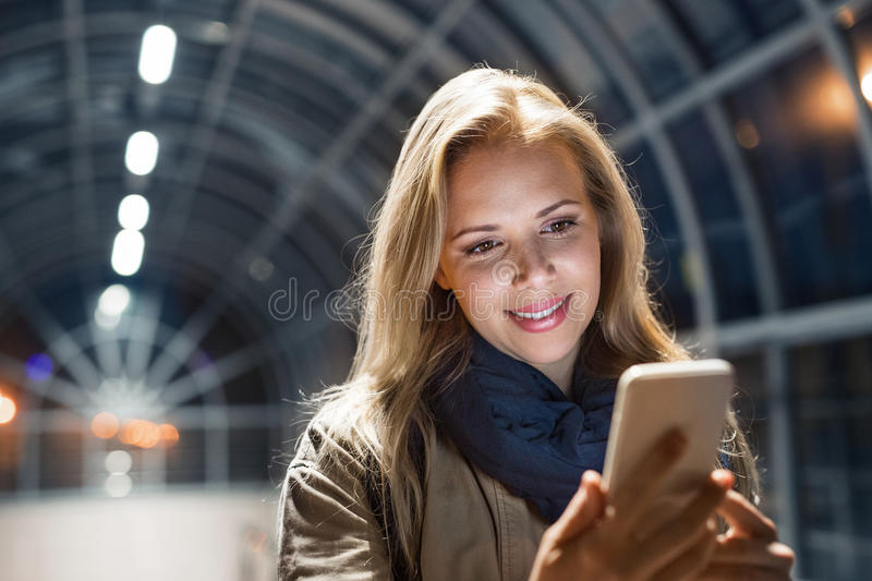 Woman in the city at night holding smartphone, texting. stock images