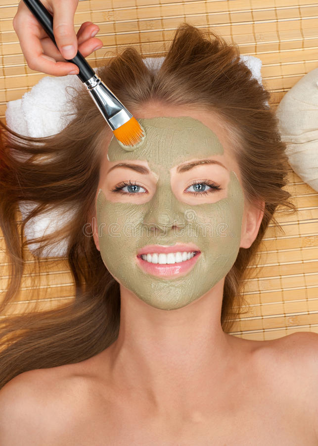 Woman with clay facial mask. Close-up of young beautiful woman with clay facial mask at spa salon stock image