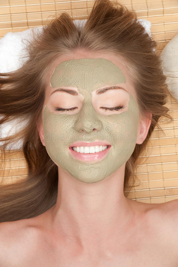 Woman with clay facial mask. Close-up of young beautiful woman with clay facial mask at spa salon stock photos