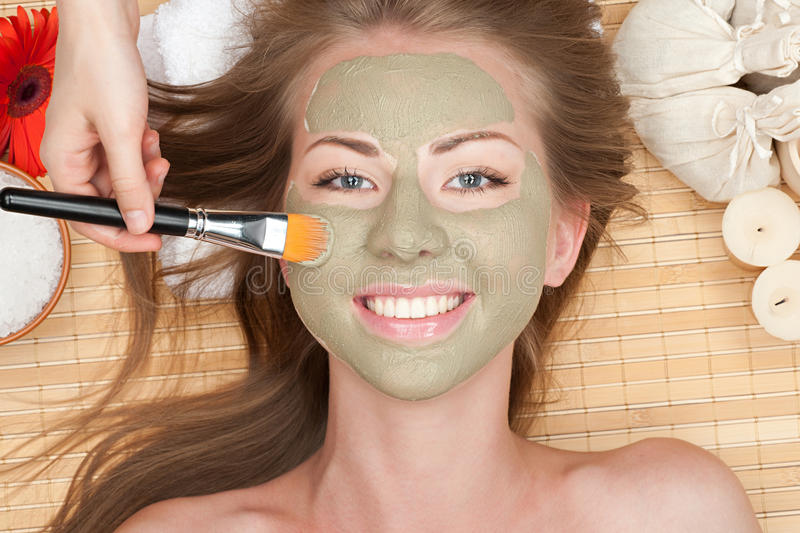 Woman with clay facial mask. Close-up of young beautiful woman with clay facial mask at spa salon royalty free stock photography