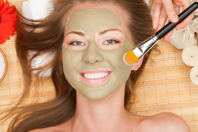 Woman with clay facial mask. Close-up of young beautiful woman with clay facial mask at spa salon royalty free stock image