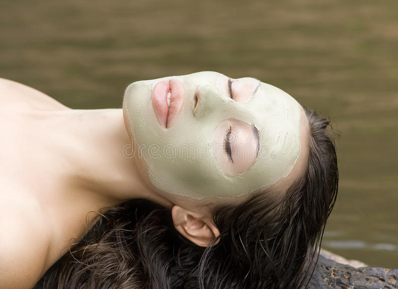 Woman with clay facial mask in beauty spa (Outdoor). Spa Outdoor, Beautiful young woman lying with natural clay facial mask on her face stock photography