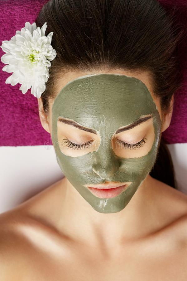 Woman with clay facial mask in beauty spa. Skincare. Beauty Concept. Facial treatment. Cosmetology. Body care girl stock photography