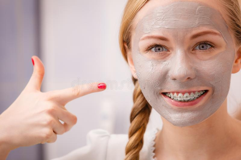 Woman with clay mud mask on her face. Skincare. Young positive woman with grey clay mud mask on her face. Female taking care of skin condition. Spa beauty stock photo