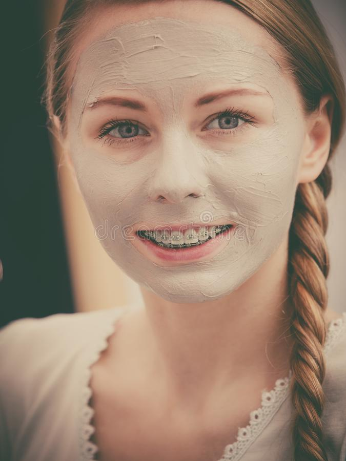 Woman with clay mud mask on her face. Skincare. Young positive woman with grey clay mud mask on her face. Female taking care of skin condition. Spa beauty stock photography