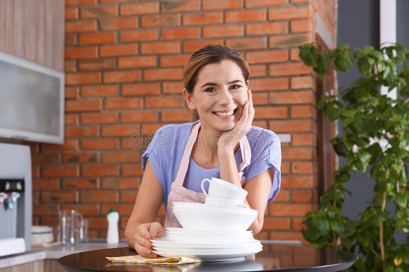 Woman with clean dishes at table royalty free stock images