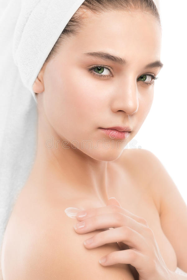 Woman with clean face and towel on her head applying moisturizer cream at shoulders. Isolated. royalty free stock image