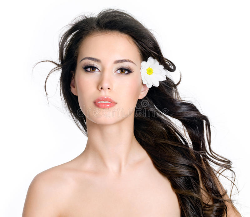 Woman with clean skin and flowers in her long hair