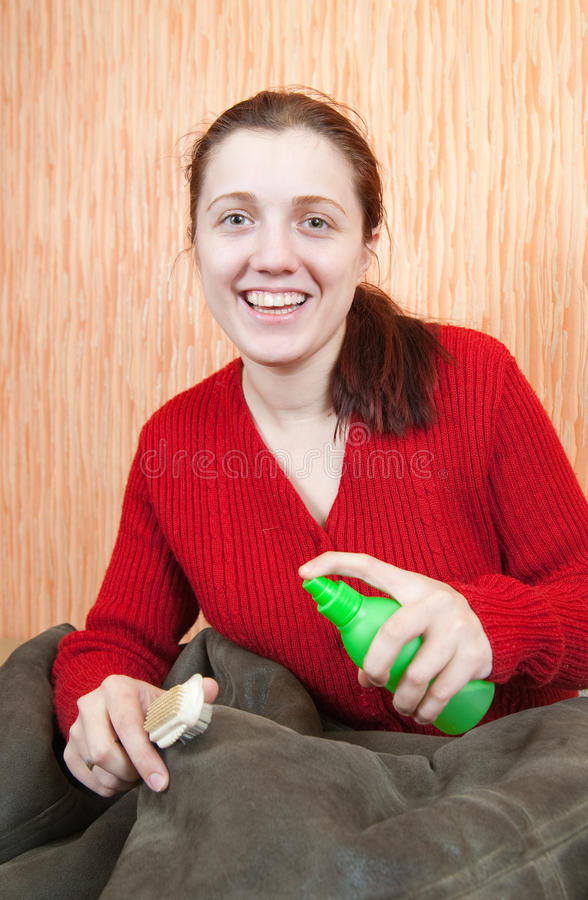 Free Woman Cleaning A Sheepskin With Whisk Broom Stock Photos - 14572493