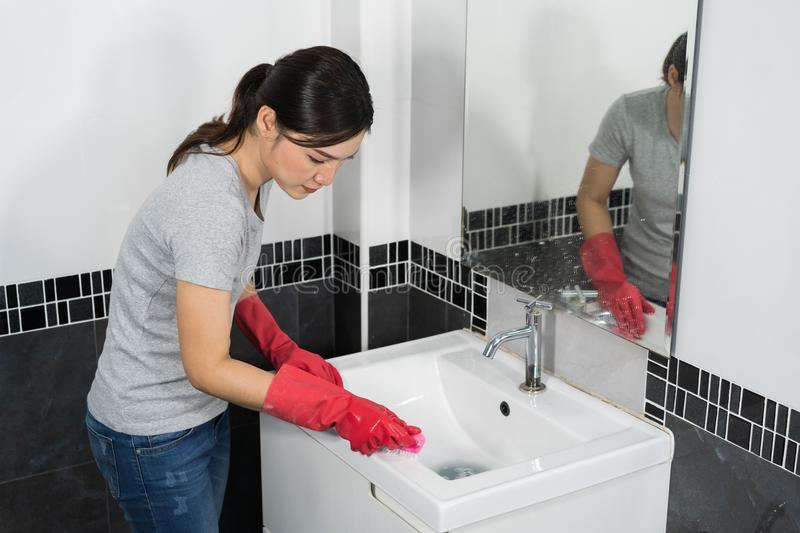 Woman cleaning bathroom sink with brush stock photos