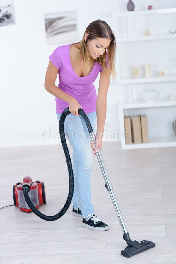 Woman cleaning carpet with vacuum cleaner stock image