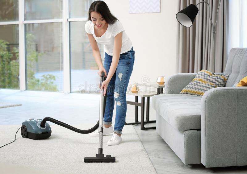Woman cleaning carpet with vacuum in room stock image