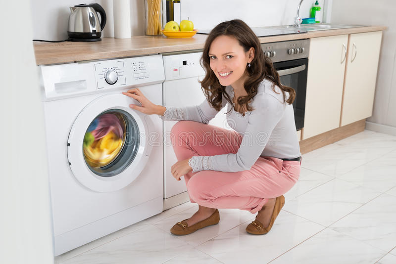 Woman Cleaning Clothes In Washing Machine stock images