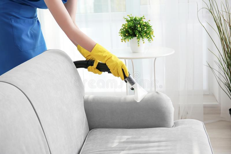 Woman cleaning couch with vacuum cleaner. At home royalty free stock image