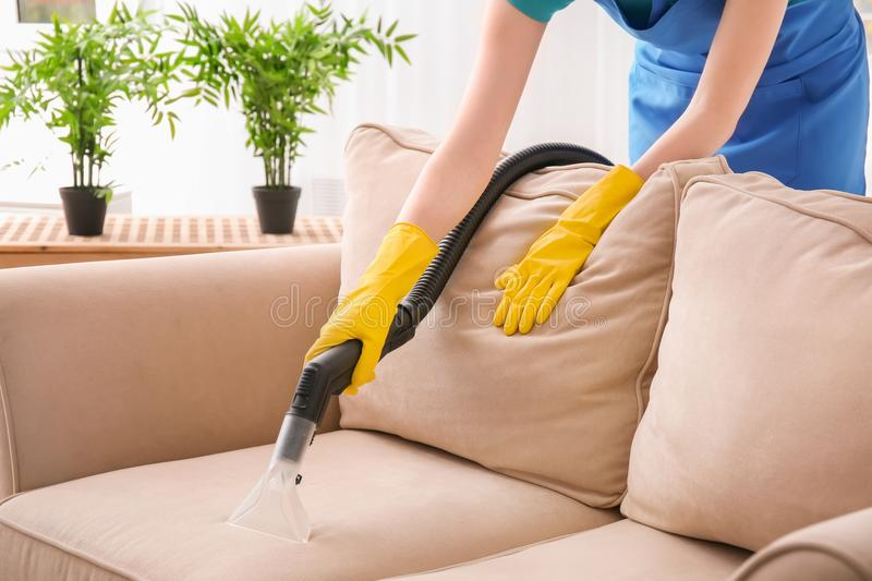 Woman cleaning couch with vacuum cleaner. At home stock images