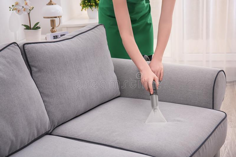 Woman cleaning couch with vacuum cleaner. At home stock photography