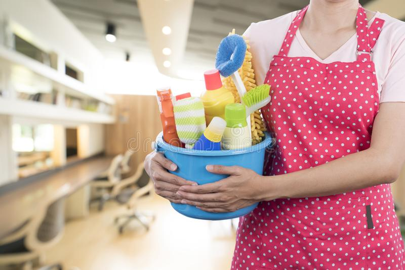 Woman with cleaning equipment ready to clean house. On living room background royalty free stock photography