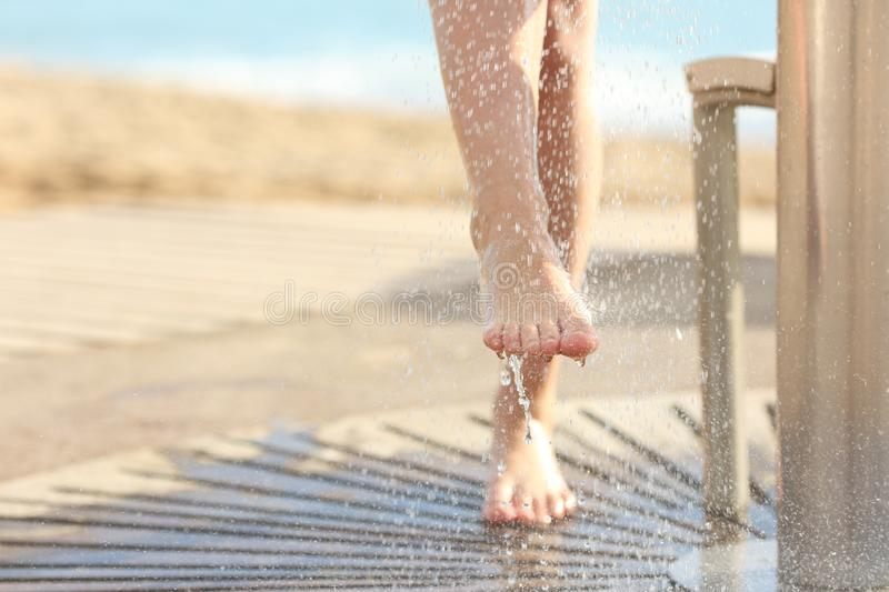 Woman cleaning feet in a shower after beach day royalty free stock photos