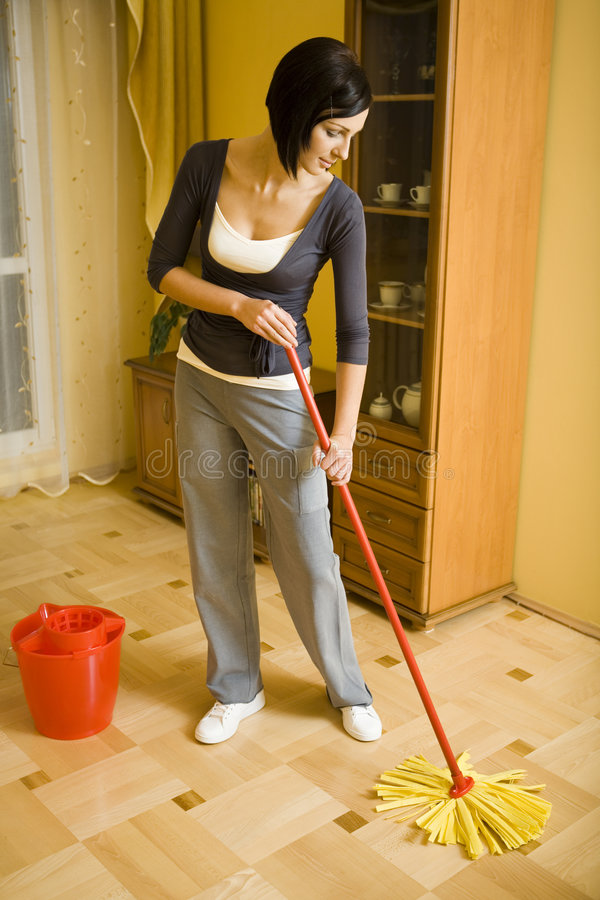 Woman cleaning floor. Young woman with the mop wipes the floor in room. Whole body. Front view stock images
