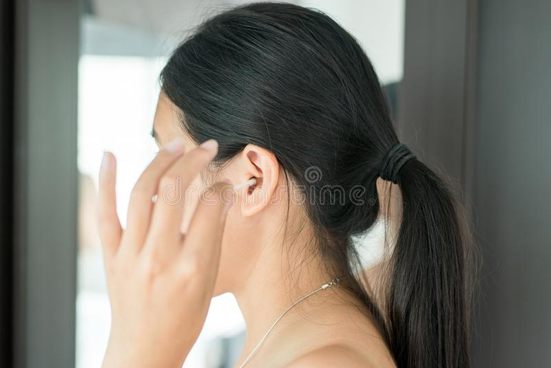 Woman cleaning her ears with cotton bud in bedroom,Female using cotton stick. Asian woman cleaning her ears with cotton bud in bedroom,Female using cotton stick royalty free stock photo