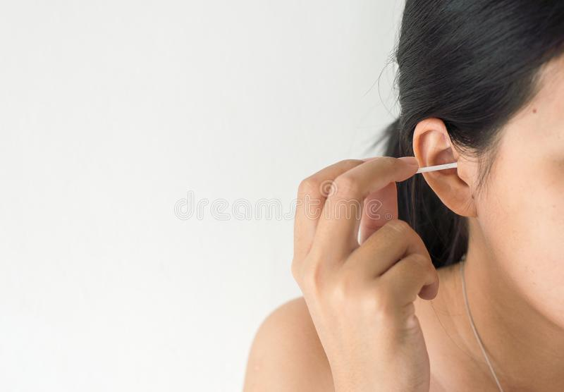 Woman cleaning her ears with cotton bud in bedroom,Female using cotton stick. Selective focus stock photography