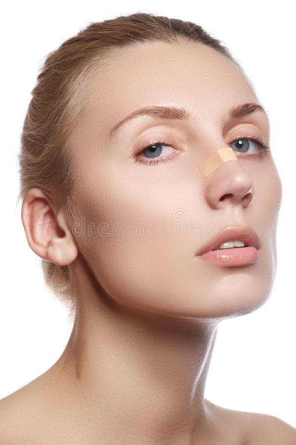 Woman cleaning her face. Beautiful young woman with clear-up patches or plaster on her nose looking at camera. Skin care concept royalty free stock photography