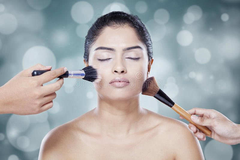Woman cleaning her face with brush stock image