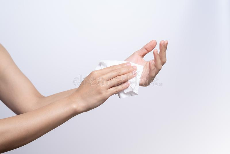 Woman cleaning her hands with white soft tissue paper. isolated on a white backgrounds royalty free stock image