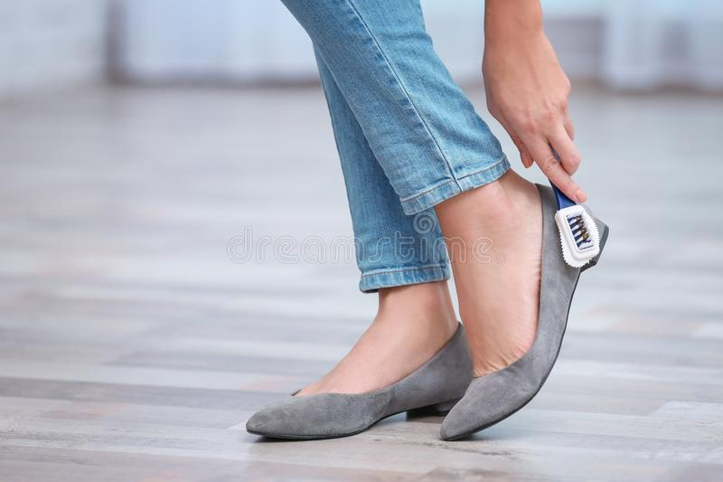 Woman cleaning her shoes with brush indoors royalty free stock photo