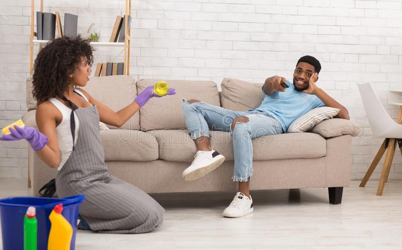 Woman cleaning home while her boyfriend resting on couch stock photo
