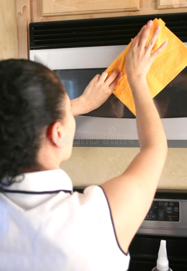 Woman cleaning microwave royalty free stock photography