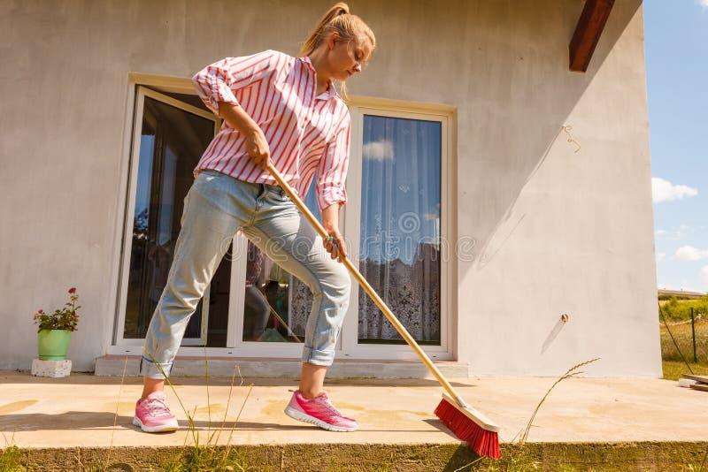 Woman cleaning patio using brush broom stock photo