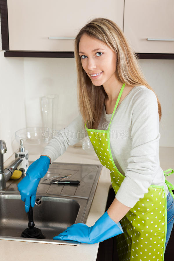 Woman cleaning pipe with plunger royalty free stock photo