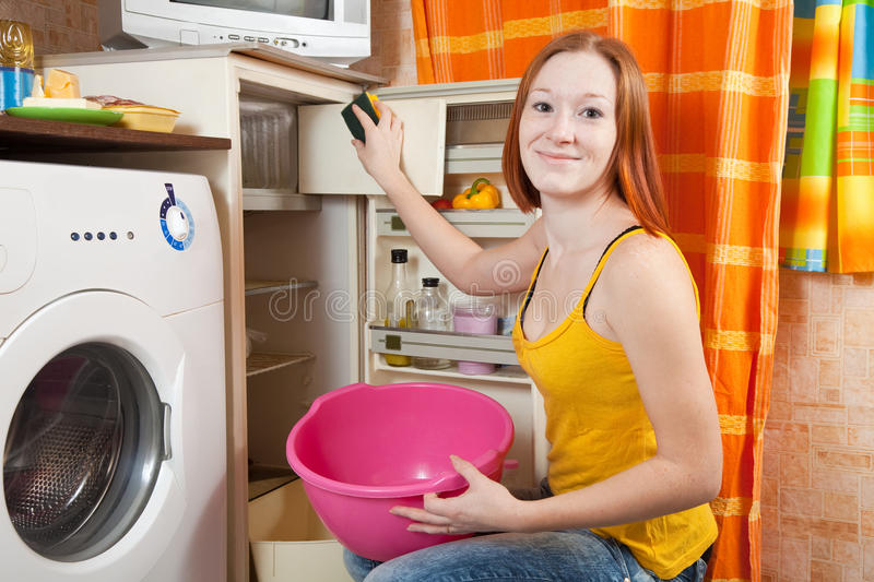 Woman cleaning the refrigerator royalty free stock images