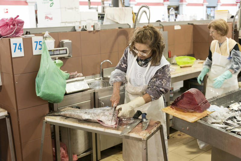 Woman cleaning, filleting fish in covered fish market
