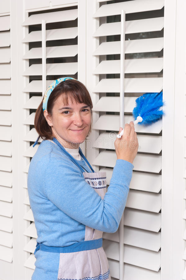 Woman cleaning shutters. A woman dusting her dirty window shutters stock photos
